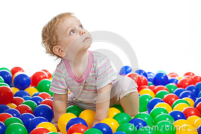 Cute kid playing colorful balls looking up