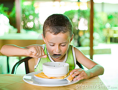 Cute kid eating soup