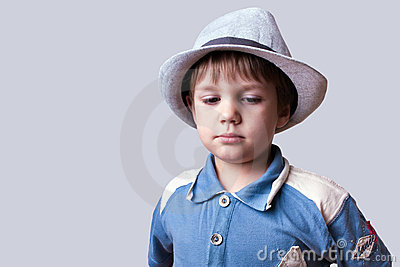 Cute kid with hat looking down