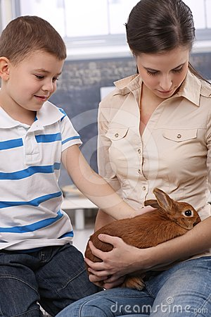 Cute kid and mum with pet bunny