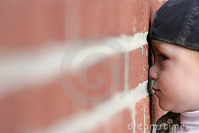Cute kid with nose squished against brick wall
