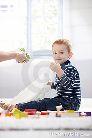 Cute kid packing toys to plastic bag