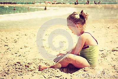 Cute kid playing at the beach. filtered image, retro style