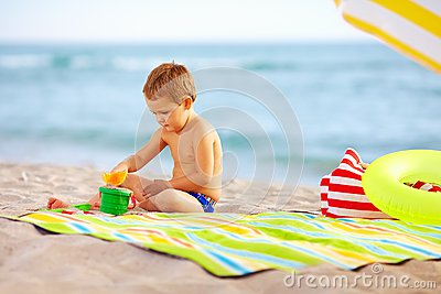Cute kid playing in sand on the beach