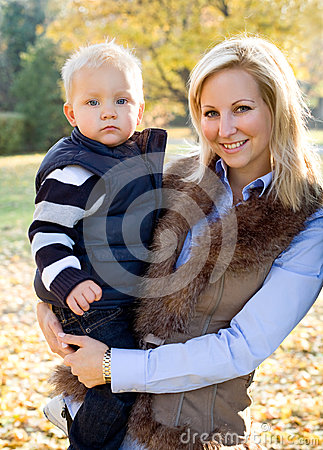 Cute kid and pretty mom outdoors at fall.