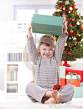 Cute kid raising christmas gift high
