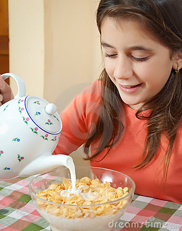 Cute latin girl eating breakfast at home