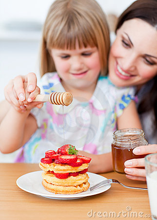 Free Cute Lgirl And Her Mother Putting Honey On Waffles Stock Image - 13258451