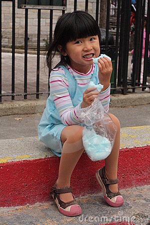 cute little asian chinese girl eating cotton candy