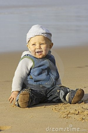 Cute little baby boy playing on the beach