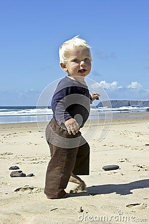 Cute little baby boy running on the beach