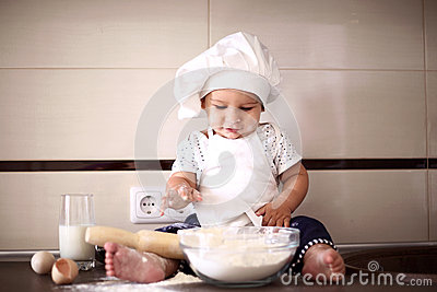 Cute little baby in a cook cap laughs