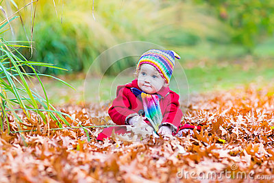 Cute little baby girl in a red coat in autumn park