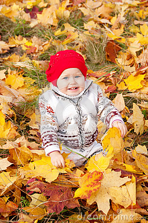 Cute little baby girl sitting on rug in the woods.