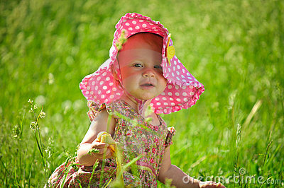 Cute Little baby in hat sitting in the grass