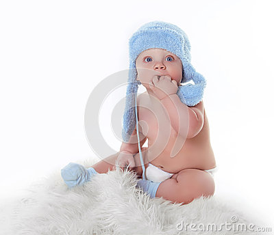 Cute little baby is looking and wearing blue hat
