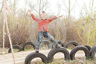 Cute little boy balanced on old tyres