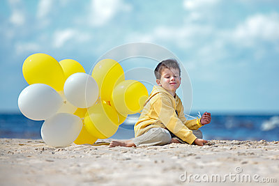 Cute little boy with balloons on the beach