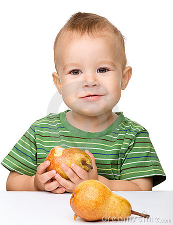 Cute little boy is eating pear