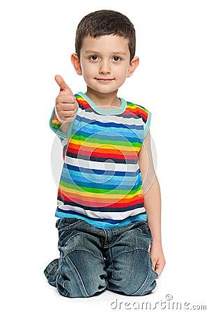 Cute little boy holding thumb up