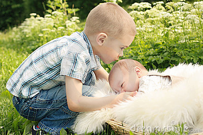 Cute little boy kissing brother outside