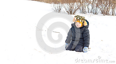 Cute little boy kneeling in winter snow
