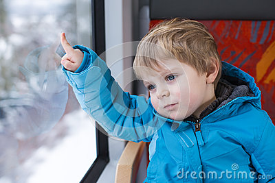 Cute little boy looking out train window