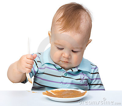 Cute little boy is playing with fruit puree