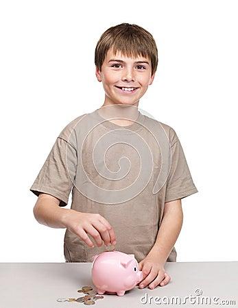 Cute little boy saving his money in a piggy bank