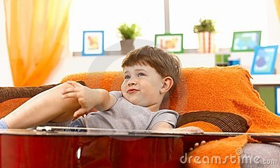 Cute little boy thinking on couch