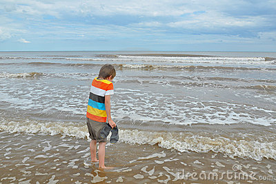 Cute little boy tries cold water in waves on beach