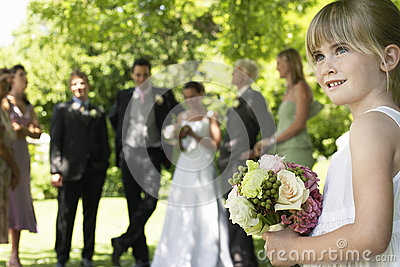 Cute Little Bridesmaid Holding Bouquet In Lawn