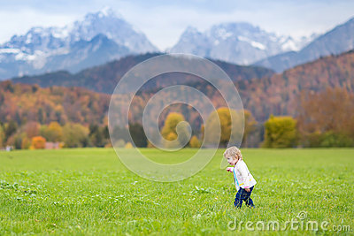 Cute little girl in beautiful field in the Alps mountains