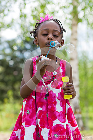 Cute little girl blowing soap bubbles