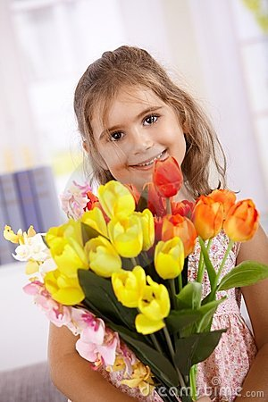 Cute little girl with bouquet of flowers smiling