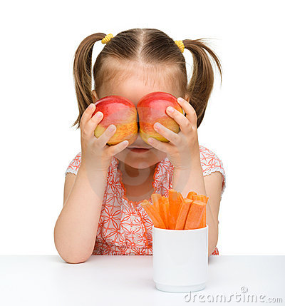 Cute little girl with carrot and apples