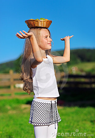 Cute little girl carrying fruit basket on head