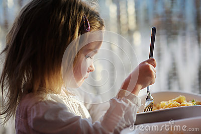 Cute little girl eating pasta