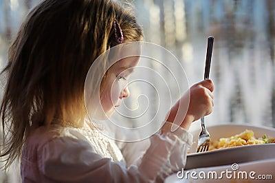 Cute little girl eating pasta