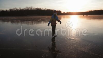 Cute little girl is going skate outdoors at sunset. A schoolgirl enjoying ice skating at frozen lake in winter season. Winter sports stock video footage