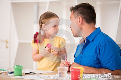 Cute little girl and her father painting together