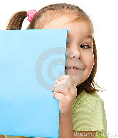 Cute little girl is hiding behind a book