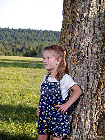 Cute Little Girl Hiding behind tree