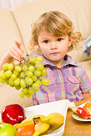 Cute little girl hold grapes fruit bowl