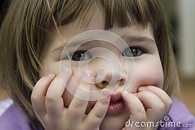 Cute little girl holding face