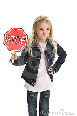Cute little girl holding a stop sign and smirking
