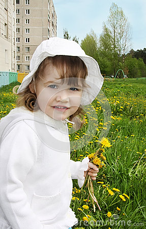 Cute little girl holds yellow dandelions