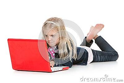 Cute little girl lying down using a laptop