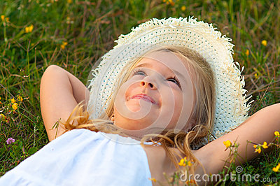 Cute little girl lying on the meadow and daydreami