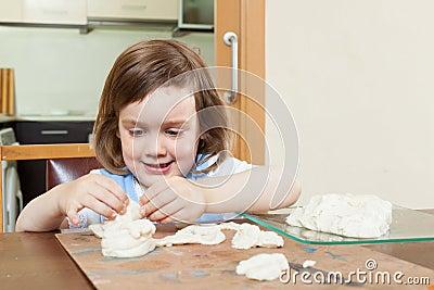 Cute little girl making dough figurines Stock Photo
